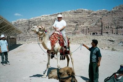 Robert W. Holloway riding a camel at Petra, Jordan.