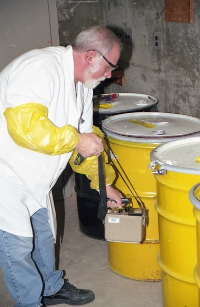 Chuck Surre, a University of Rochester radiation safety technician is shown here performing a radiation survey around some drums of just-compacted radioactive waste in the waste storage room.
