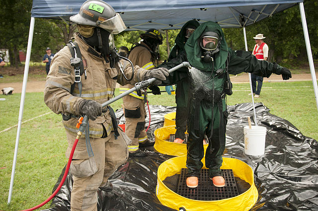 Firefighter Decontaminates a Soldier