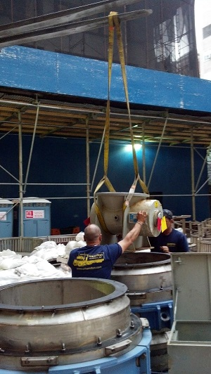 Workers are loading an irradiated source into a Type B container for shipping.